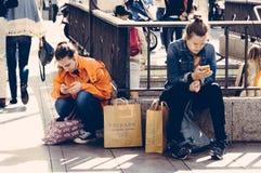 Frauen, die auf der Straße mit den Einkaufstaschen simsen auf ihrem sitzen Stockfotografie