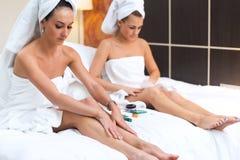 Frauen, die auf einem Bett anwendet Feuchtigkeitscremesahnebeine sitzen Stockfotografie