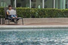 Frauen, die auf einem Laptop durch das Pool sitzen lizenzfreie stockfotos