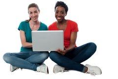 Frauen, die auf Laptop grasen Lizenzfreie Stockfotografie