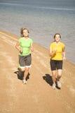 Frauen, die auf Strand laufen Lizenzfreies Stockfoto