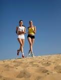 Frauen, die auf Strand laufen Lizenzfreie Stockbilder