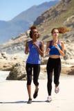 Frauen, die auf Strand laufen Lizenzfreies Stockbild