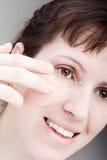 Frauen, die Augenhautsahne auftragen Stockfoto