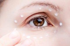 Frauen, die Augenhautsahne auftragen Stockfotos
