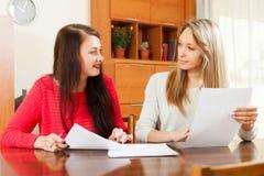 Frauen, die bei Tisch Dokumente schauen Lizenzfreie Stockfotografie