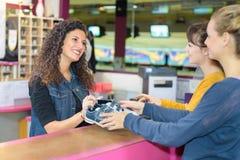 Frauen, die Bowlingspielschuhe an der Bowlingbahn mieten Lizenzfreie Stockbilder