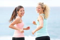 Frauen, die das Lächeln auf Strand ausübend laufen Stockfoto