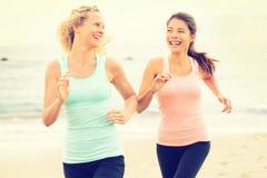 Frauen, die das Rütteln ausübend glücklich auf Strand laufen Lizenzfreie Stockfotos