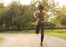 Frauen, die das Trainieren ihr Bein ausdehnen, entspannen sich, um für das Laufen mitzumischen Stockbild