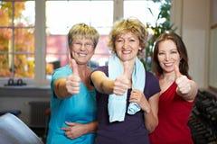 Frauen, die Daumen oben in der Gymnastik anhalten Stockbild