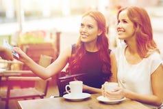 Frauen, die dem Kellner Geld für Kaffee am Café zahlen Lizenzfreies Stockfoto
