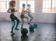 Frauen, die in der Aerobicklasse trainieren Stockbilder
