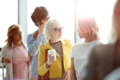 Frauen, die in der Flughafenreihe sprechen stockfoto