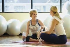 Frauen, die an der Gymnastik sitzen und gesellig sind stockbilder