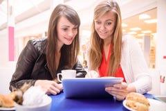 Frauen, die digitale Tablette beim Essen des Kaffees und der Snäcke verwenden Lizenzfreies Stockfoto