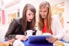 Frauen, die digitale Tablette beim Essen des Kaffees und der Snäcke verwenden Stockbild