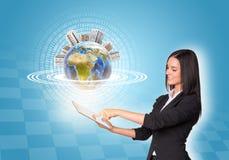 Frauen, die digitale Tablette und Erde mit verwenden Stockbild