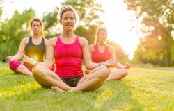 Frauen, die draußen Yoga bei Sonnenuntergang tun Stockbilder