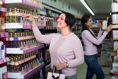 Frauen, die Duft im Speicher vorwählen lizenzfreie stockfotografie