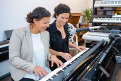 Frauen, die Duo auf Tastatur spielen stockbild