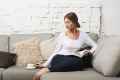 Frauen, die ein Buch auf Sofa lesen Lizenzfreie Stockbilder