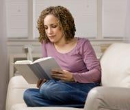 Frauen, die ein Buch im Wohnzimmer lesend genießen Lizenzfreie Stockbilder