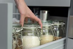 Frauen, die ein Einzelteil vom Speicherkaninchenstall auswählen Intelligentes Küchenorganisationskonzept stockbild