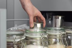 Frauen, die ein Einzelteil vom Speicherkaninchenstall auswählen Intelligentes Küchenorganisationskonzept stockbilder
