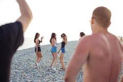 Frauen, die entlang Küstenlinie schlendern Freundinnen, die zusammen auf den Strand, Sommerferien genießend gehen stockfoto
