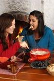 Frauen, die Fondue essen Stockfoto