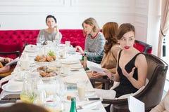 Frauen, die an gedientem Tisch sitzen Lizenzfreies Stockfoto