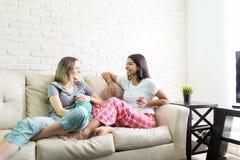 Frauen, die Geheimnisse von Freunden beim Genießen der Pyjama-Partei aufdecken stockfoto