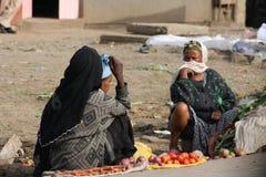 Frauen, die Gemüse auf Telefonverkehr verkaufen Stockbild