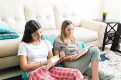 Frauen, die Geschichten im Roman im Wohnzimmer lesen stockfotografie