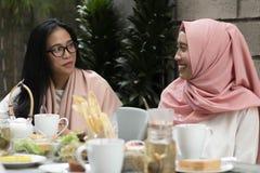 Frauen, die Gespräch in der Mitte des Mittagessens haben stockfotos