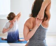Frauen, die gomukhasana in der Yogaklasse üben Lizenzfreies Stockbild