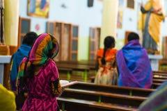 Frauen, die Gott durch Ablesenbuchpastor und betenden Gott der Leute in der Kirche beten stockfoto