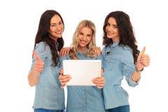 3 Frauen, die gute Nachrichten auf einem Tablettenauflagencomputer lesen Lizenzfreies Stockfoto