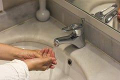 Frauen, die ihre Hände in der Wanne am Badezimmer waschen stockfoto