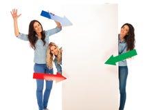 3 Frauen, die ihre Pfeile auf ein großes leeres Brett zeigen Stockfotografie