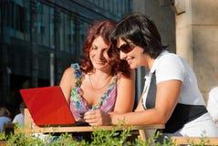 Frauen, die innen in einem Kaffee in die Stadt sitzen Lizenzfreies Stockfoto