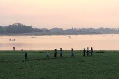 Frauen, die Körbe auf ihren Köpfen am Taungthaman See tragen Lizenzfreie Stockfotos