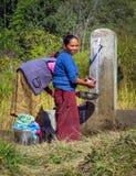 Frauen, die Kleidung an einem Hahn des öffentlichen Wassers in einem kleinen Bergdorf, Nepal waschen lizenzfreie stockbilder