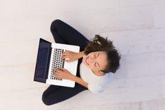 Frauen, die Laptop-Computer auf der Draufsicht des Bodens verwenden Stockbild