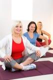 Frauen, die mit überkreuzten Beinen auf Matte sitzen Stockfotos