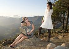 Frauen, die mit beweglichem Laptop im Berg arbeiten Stockfotos