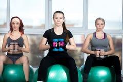 Frauen, die mit Dummköpfen auf Bällen ausarbeiten Stockfoto