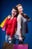 Frauen, die mit vielen Taschen auf Blau kaufen Stockfotos