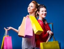 Frauen, die mit vielen Taschen auf Blau kaufen Stockfoto